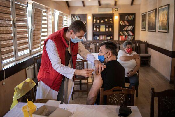 Muž dostává dávku čínské vakcíny Sinopharm v restauraci v srbském Kragujevaci - Sputnik Česká republika