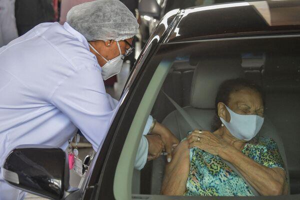 Žena dostavá vakcínu, když  projíždí přes očkovací centrum na stadionu Pacaembu v brazilském São Paulu. - Sputnik Česká republika