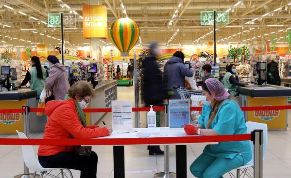 Žena vyplňuje papíry před očkováním proti covidu-19 ruskou vakcínou Sputnik V (Gam-COVID-Vac) v hypermarketu Globus v Moskvě - Sputnik Česká republika