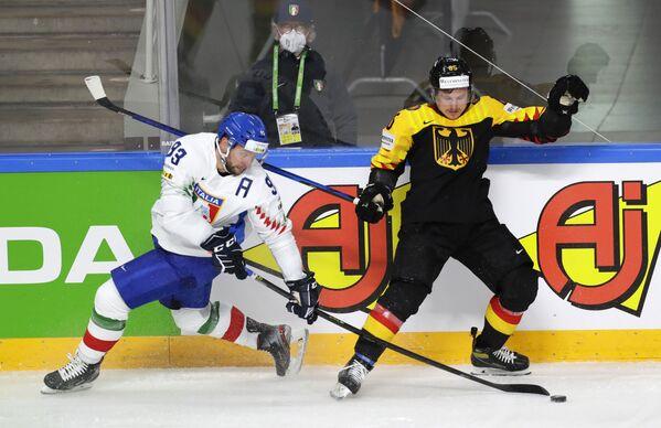 Italský hokejista Markus Gander bojuje o puk s německým hráčem Marcelem Brandtem v zápase skupinové fáze Mistrovství světa v ledním hokeji 2021 mezi národními týmy Německa a Itálie. - Sputnik Česká republika