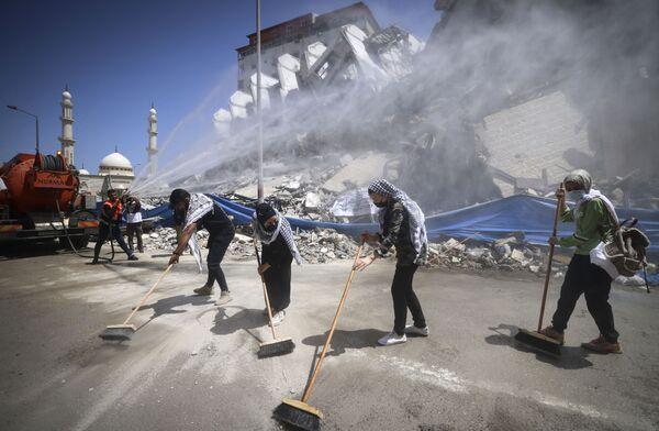 Dobrovolníci a pracovníci komunálních služeb uklízí hromadu trosek po izraelském raketovém útoku v Pásmu Gazy  - Sputnik Česká republika