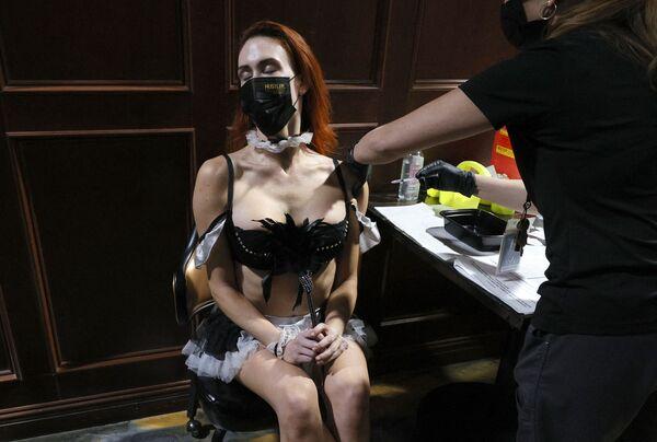 Účastnice show Sexxy After Dark JoJo Hamner se očkuje proti covidu-19 v klubu Hustler. Las Vegas, Nevada. - Sputnik Česká republika