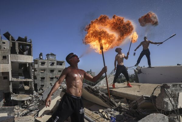 Členové Bar Woolf Team provádí triky s ohněm na pozadí zničených budov v Pásmu Gazy. - Sputnik Česká republika