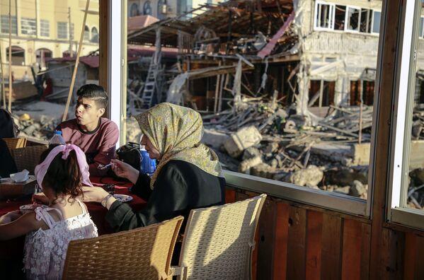 Obyvatelé Pásma Gazy na pozadí zničené budovy. - Sputnik Česká republika