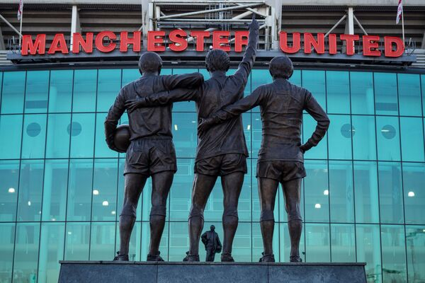 """Památník """"manchesterské trojice"""": fotbalistů Bestа, Lаwа a Charltona u budovy stadionu Old Trafford v Manchesteru. - Sputnik Česká republika"""
