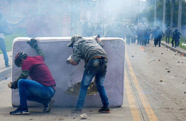 Demonstranti se kryjí za matrací během střetu s pořádkovou policií v Kolumbii   - Sputnik Česká republika
