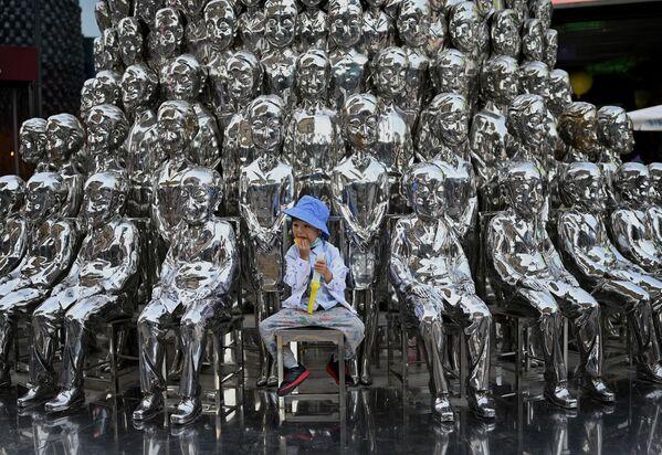 Chlapec sedí na židli mezi sochami vystavenými v nákupním centru na Mezinárodní den dětí v Pekingu - Sputnik Česká republika
