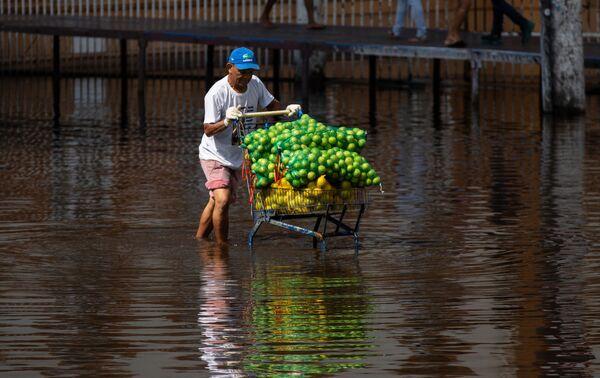 Muž tlačí vozík s ovocem, když prochází zaplavenou ulicí v centru Manausu v Brazílii - Sputnik Česká republika