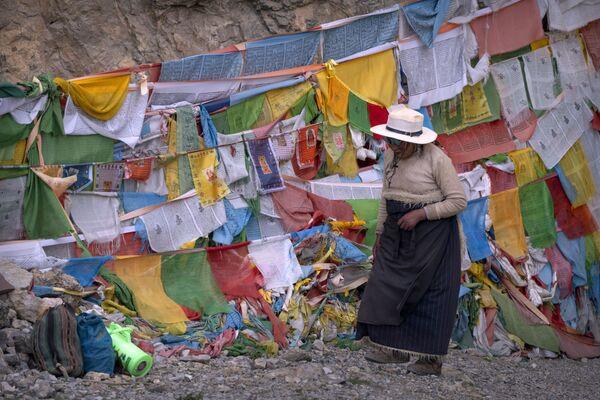 Žena prochází kolem modlitebních vlajek před buddhistickým chrámem v tibetském Namcu - Sputnik Česká republika