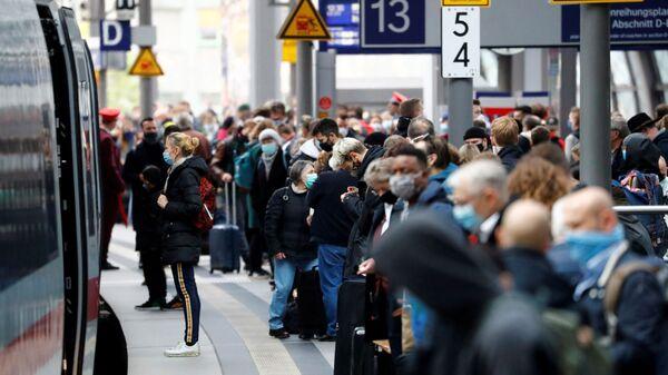 Пассажиры в масках ждут на платформе главного железнодорожного вокзала в Берлине  - Sputnik Česká republika