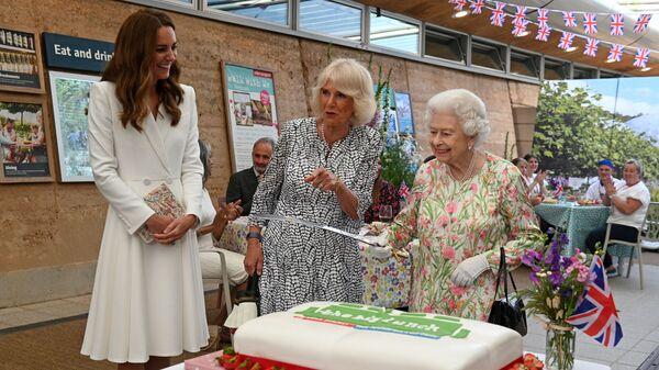 Королева Елизавета разрезает торт рядом с герцогиней Кембриджской Кэтрин и герцогиней Корнуоллской Камиллой во время приема на саммите G7 в Корнуолле - Sputnik Česká republika