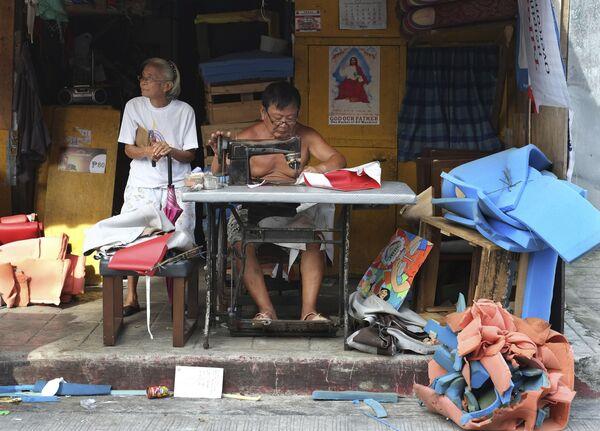 Krejčí pracuje na starém šicím stroji v silničním obchodě na předměstí Makati na Filipínách. - Sputnik Česká republika