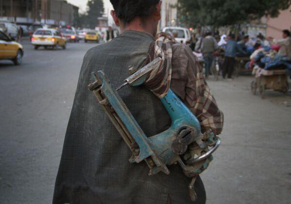 Afghánský muž nese rozbitý starý šicí stroj na prodej v Kábulu - Sputnik Česká republika