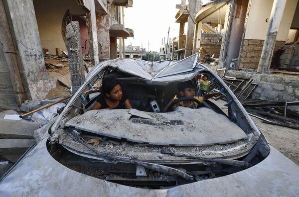 Палестинские дети играют в машине, разрушенной во время конфликта между ХАМАС и Израилем  - Sputnik Česká republika