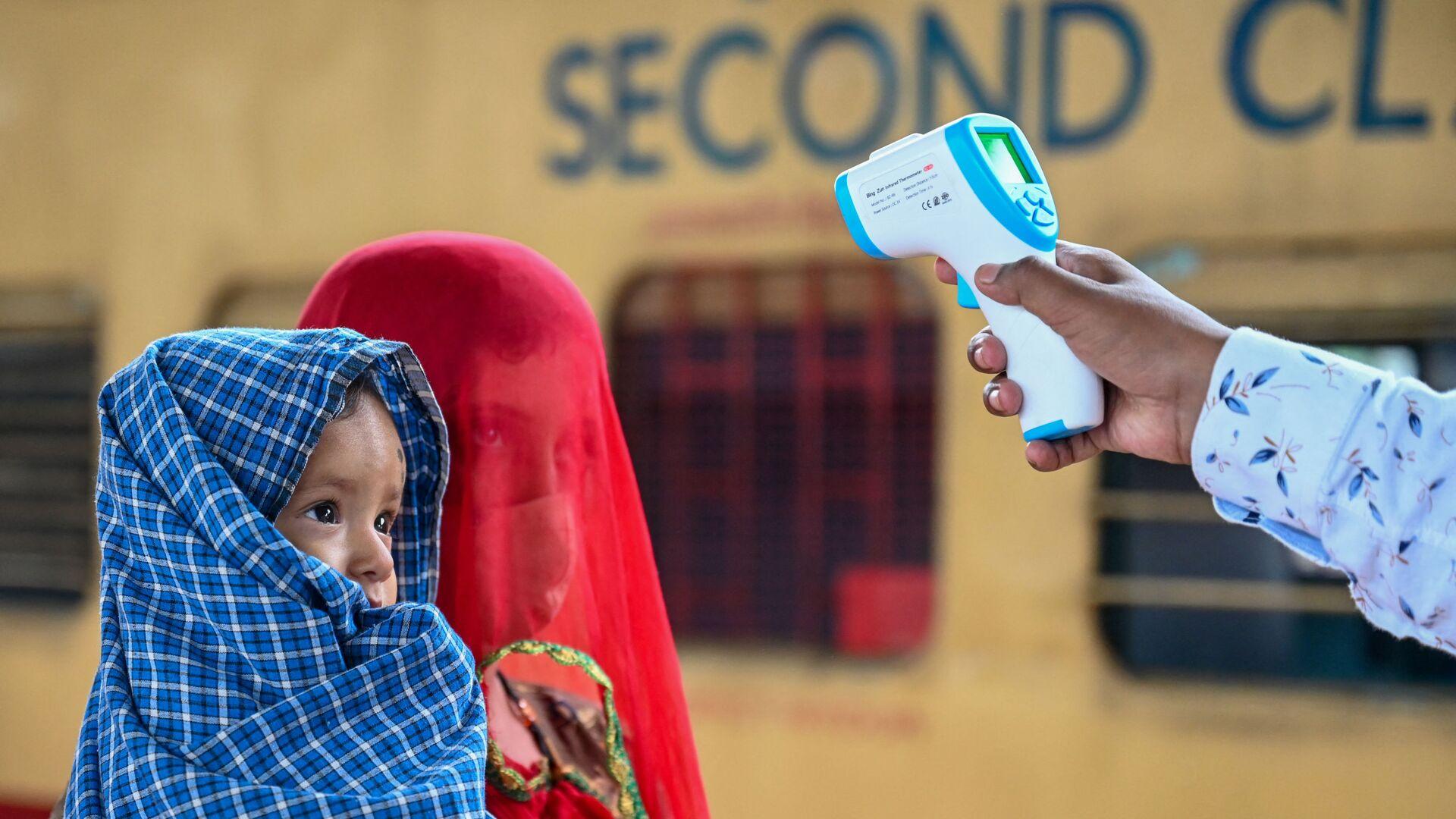 Медицинский работник проверяет температуру тела ребенка во время скрининга на коронавирус Covid-19 в Мумбаи - Sputnik Česká republika, 1920, 20.06.2021