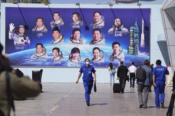 Novináři a zaměstnanci procházejí kolem billboardu zobrazujícího čínské astronauty, kosmodrom Ťiou-čchüan v severozápadní Číně. - Sputnik Česká republika