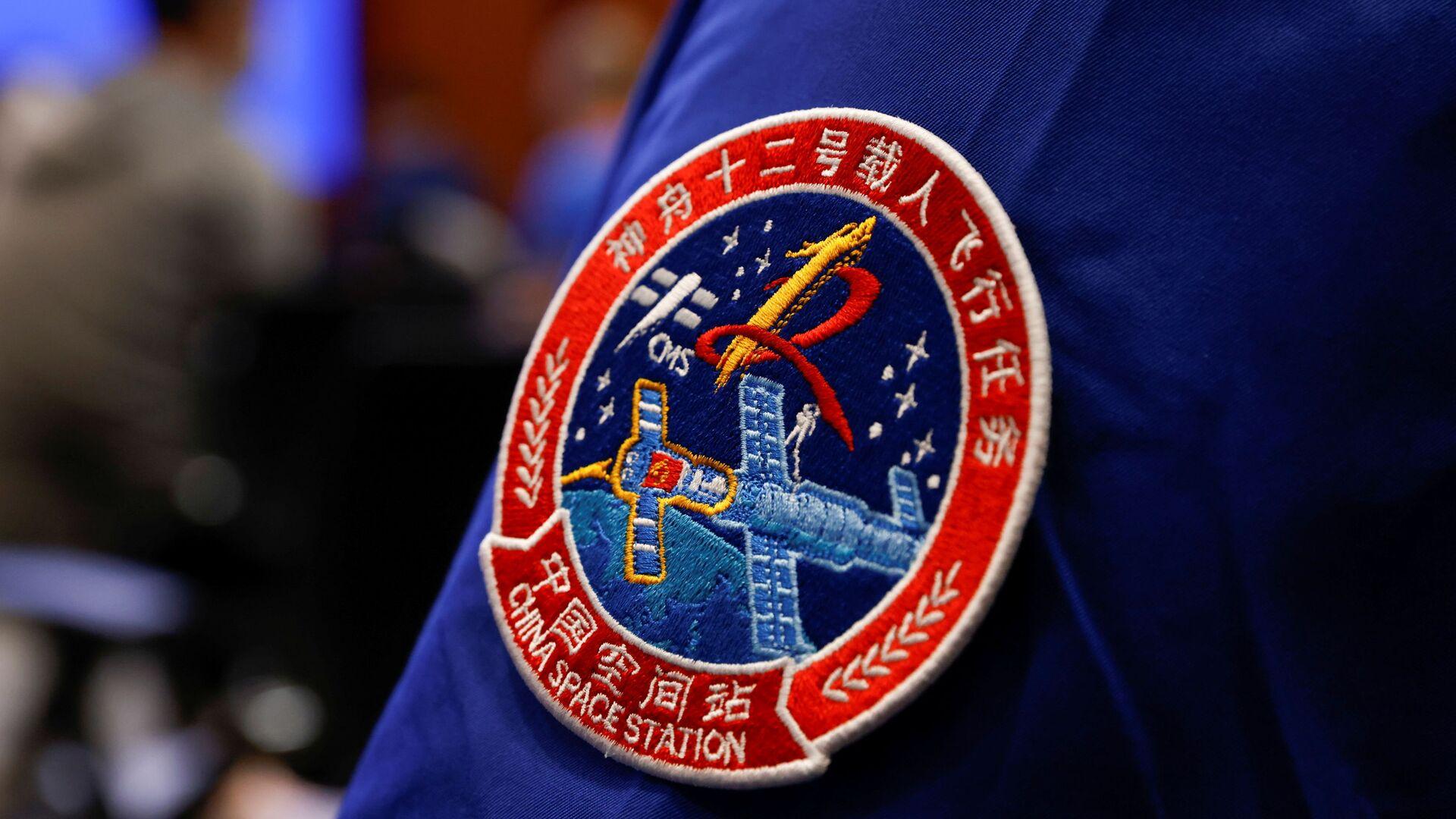 Нашивка с изображением космического полета Шэньчжоу-12 на штатном сотруднике в Китае  - Sputnik Česká republika, 1920, 17.06.2021