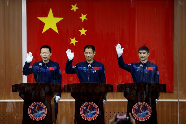 Čínští astronauti Nie Haisheng, Liou Boming a Tang Hongbo za skleněnou stěnou mávají novinářům. - Sputnik Česká republika