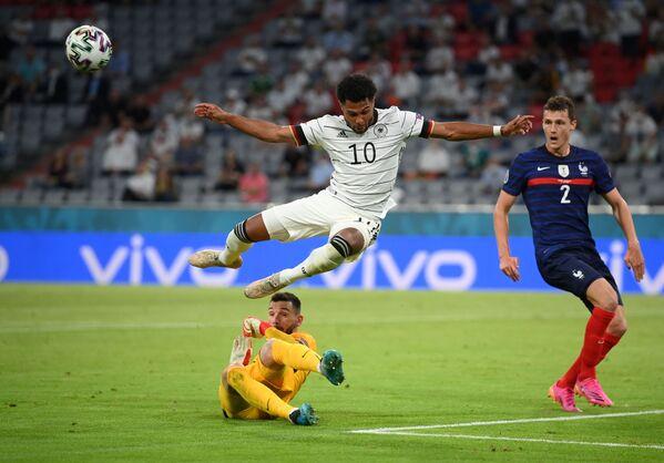 Německý fotbalista Serge Gnabry a francouzský hráč Hugo Lloris. - Sputnik Česká republika