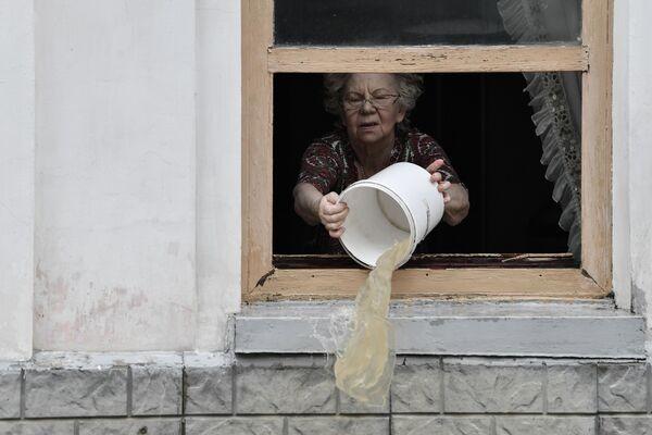 Žena odstraňuje následky silných dešťů, které způsobily v Kerči potopy. - Sputnik Česká republika