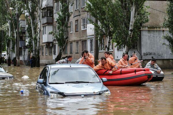 Lidé proplouvají ulicí v Kerči na gumovém člunu.  - Sputnik Česká republika