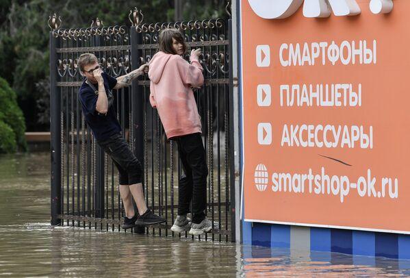 Mladí lidé v Kerči se snaží obejít vysokou vodu a šplhají po zábradlí.   - Sputnik Česká republika