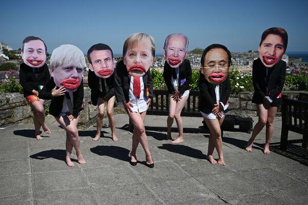 Environmentální aktivisté Extinction Rebellion vystupují s tvářemi vůdců G7 na demonstraci, která má zdůraznit nerovnost pohlaví v politice. Demonstrace se odehrála během summit G7 13. června 2021v St. Ives v Cornwallu.  - Sputnik Česká republika