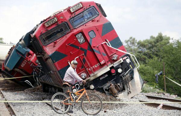 Muž na kole projíždí kolem vykolejeného vlaku. K neštěstí došlo15. června v Mexiku ve městě San Isidro Mazatepec. Jeden člověk zemřel a tři další utrpěli zranění.  - Sputnik Česká republika
