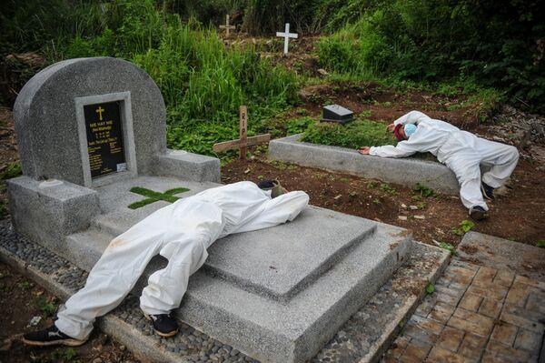 Pracovníci v ochranných oděvech odpočívají poté, co pohřbili oběť covidu-19 v Indonésii.  - Sputnik Česká republika