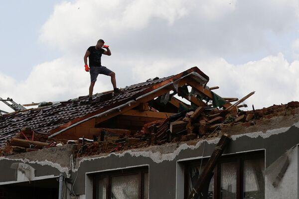 Muž uklízí střechu poškozené budovy po tornádu v obci Moravská Nová Ves - Sputnik Česká republika