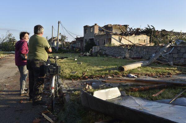 Místní obyvatelé sledují poškozené domy poté, co tornádo zasáhlo vesnici Moravská Nová Ves na jižní Moravě - Sputnik Česká republika
