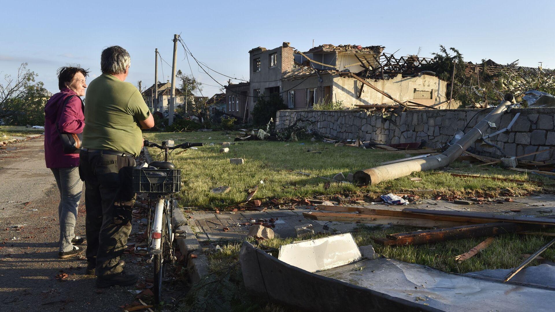 Místní obyvatelé sledují poškozené domy poté, co tornádo zasáhlo vesnici Moravská Nová Ves na jižní Moravě - Sputnik Česká republika, 1920, 02.07.2021