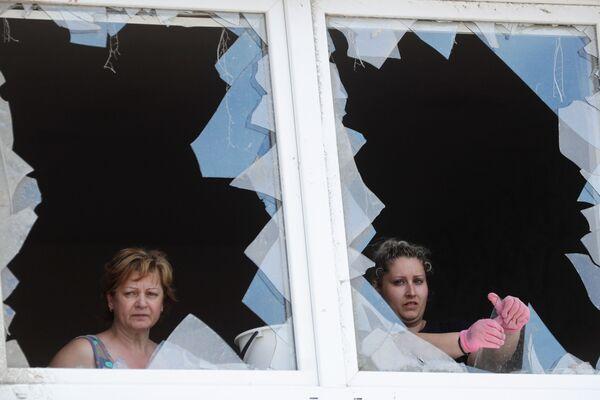 Ženy se dívají poškozenými okny budovy následkem nečekaného tornáda, které zasáhlo a zničilo části některých vesnic a měst, v obci Moravská Nová Ves - Sputnik Česká republika