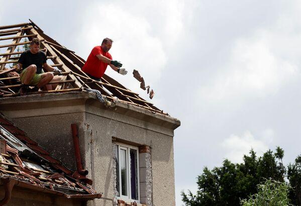 Muži odstraňují rozbité dlaždice ze střechy budovy po nečekaném tornádu v obci Moravská Nová Ves - Sputnik Česká republika