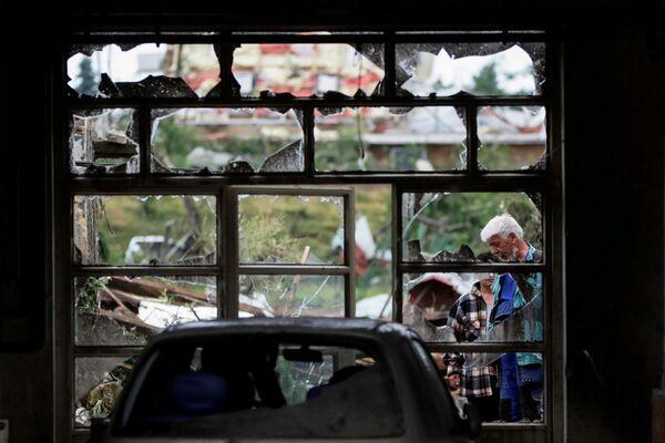 Lidé stojí u rozbitého okna po tornádu, které zasáhlo vesnici Mikulčice - Sputnik Česká republika