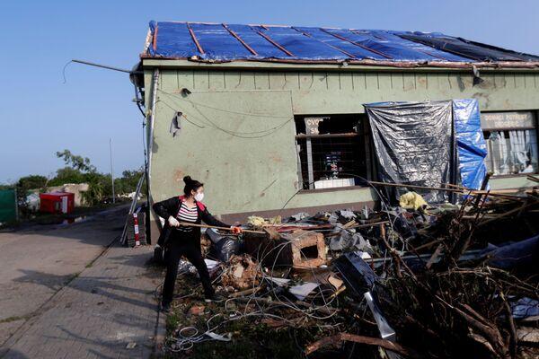 Žena zametá odpadky u poškozeného obchodu po tornádu v obci Lužice - Sputnik Česká republika