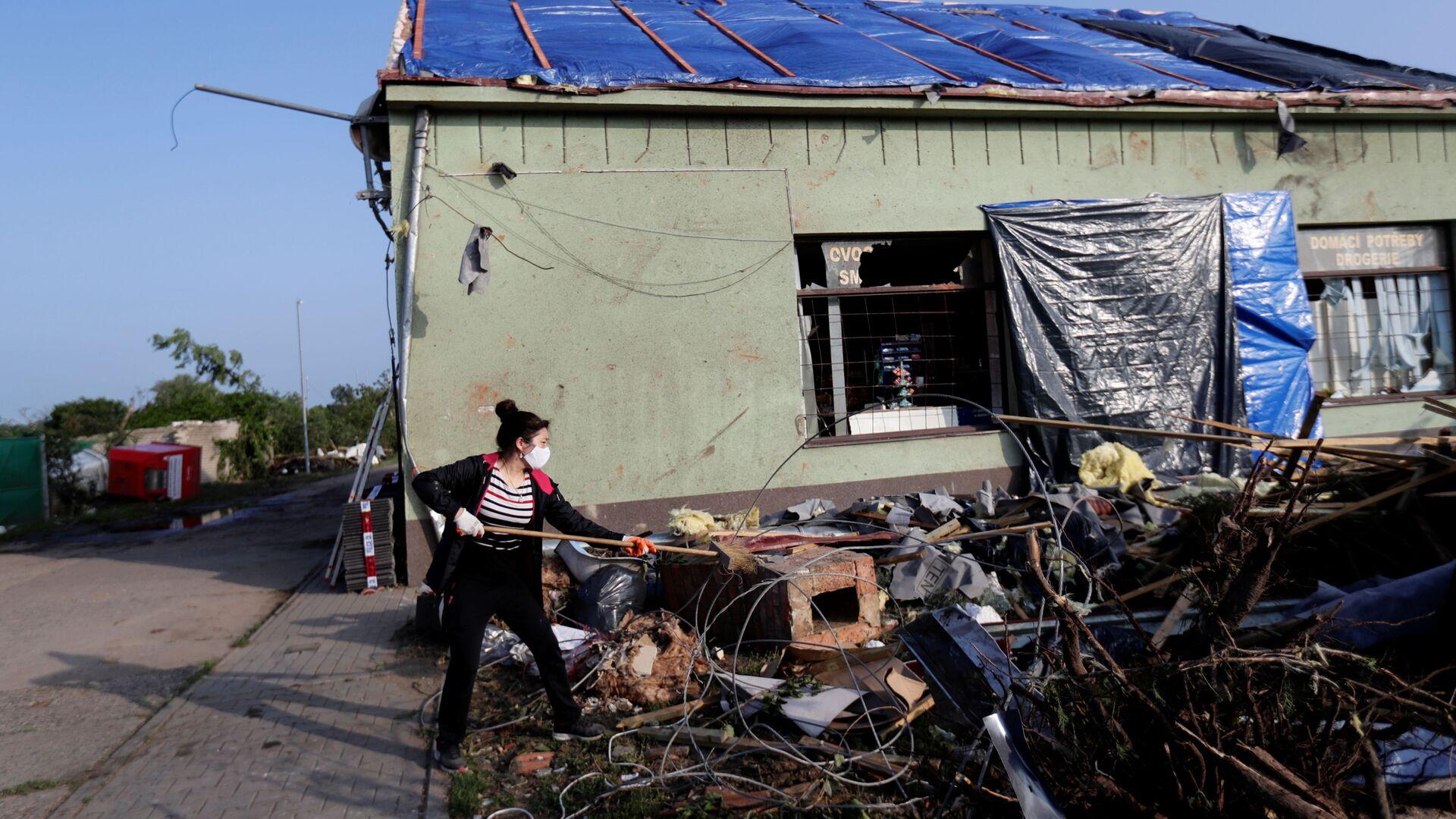 Žena zametá odpadky u poškozeného obchodu po tornádu v obci Lužice - Sputnik Česká republika, 1920, 27.06.2021