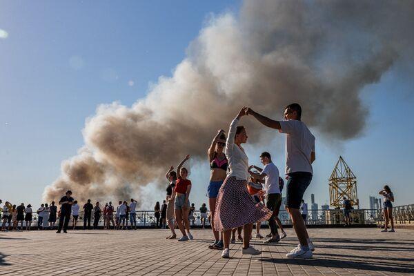 Páry tančí sambu, když stoupá kouř nad hořícím skladem pyrotechniky v Moskvě - Sputnik Česká republika