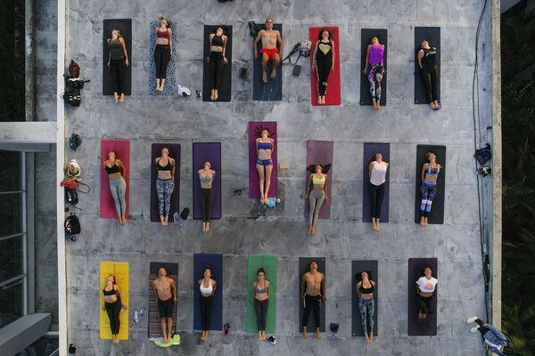 Lidé cvičí jógu na střeše studia ARA Yoga Caracas v Caracasu ve Venezuele - Sputnik Česká republika