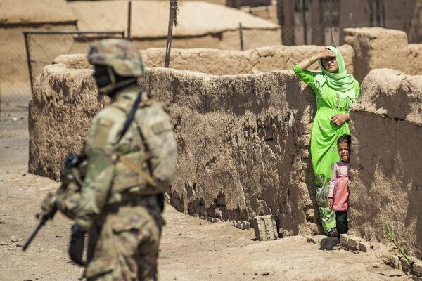 Americký voják stojí vedle ženy a dítěte během americké vojenské hlídky v Rumailanu - Sputnik Česká republika