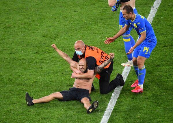 Ochranka s mužem, který vyběhl na hřiště během zápasu Švédsko-Ukrajina - Sputnik Česká republika