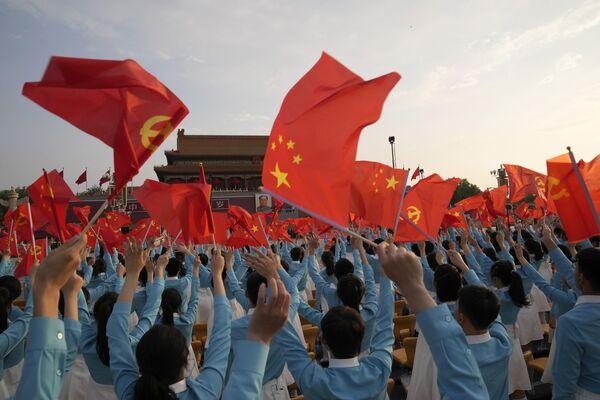 Lidé u brány Nebeského klidu v Pekingu mávají čínskou vlajkou během slavnostního ceremoniálu věnovaného 100. výročí založení vládnoucí Komunistické strany Číny.  - Sputnik Česká republika