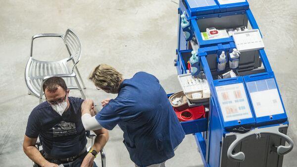 Мужчина получает дозу вакцины Pfizer в Национальном вакцинационном центре в Праге - Sputnik Česká republika