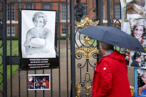 Человек смотрит на фото британской принцессы Дианы у Кенсингтонского дворца в Лондоне - Sputnik Česká republika