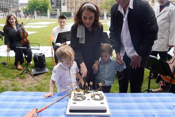 Partnerka Juliana Assangeho, Stella Morris, spolu s jejich dětmi Gabrielem a Maxem krájí narozeninový dort. - Sputnik Česká republika