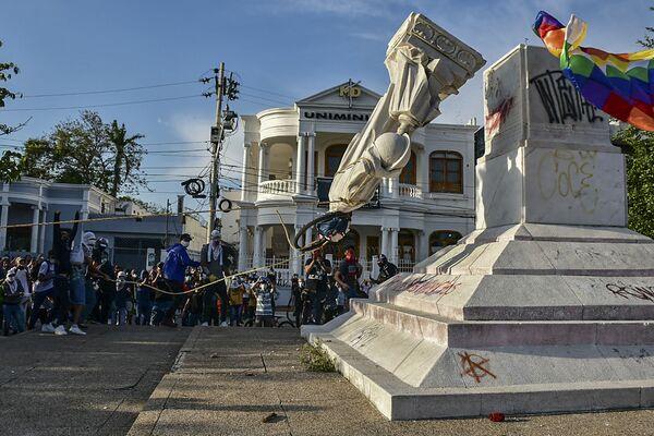 Protestující svrhávají sochu Kryštofa Kolumba během protivládních demonstrací v Kolumbii. - Sputnik Česká republika