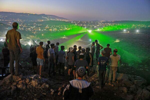 Obyvatelé izraelských osad se dívají na to, jak na ně palestinští protestující svítí laserovými paprsky z vedlejší obce Beita. - Sputnik Česká republika