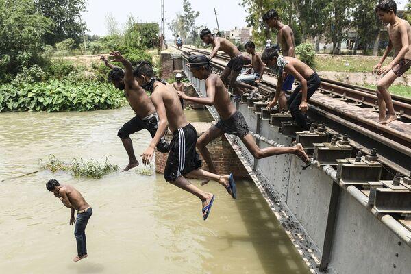 Muži skáčou do vody, aby se ochladili během vedra. Amritsar, Indie. - Sputnik Česká republika