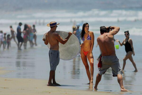 Žena v bikinách pózuje před fotografy na pláži v oblasti San Diega 4. července 2020. V tomto období bylo množství pláží v Kalifornii uzavřeno kvůli pandemii. Pláže San Diega však zůstaly otevřené.  - Sputnik Česká republika