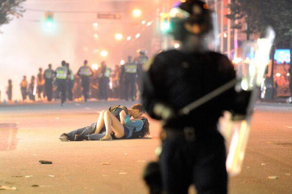 Pár se líbá před hlídkou policie ve Vancouveru v Kanadě. Ve Vancouveru propukly nepokoje poté, co hokejový tým Vancouver Canucks prohrál v zápasu na Stanley Cupu.  - Sputnik Česká republika